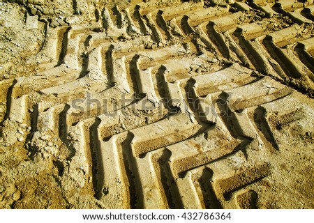 Off road tractor wheel tracks on road sand motoring background image. Industrial transport theme. - stock photo