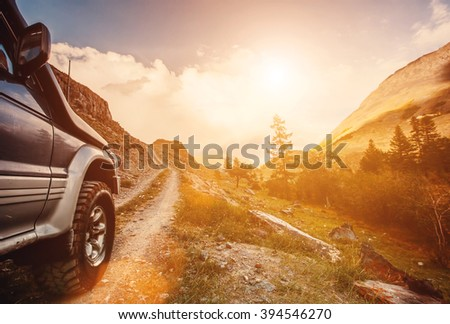 Off-road travel on mountain road. Beautiful mountains sunset - stock photo