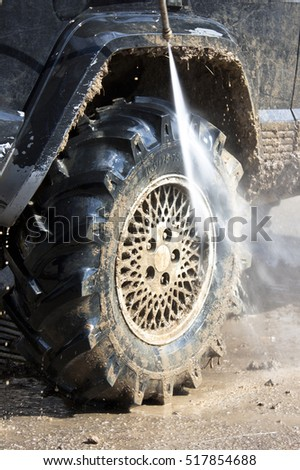 Off - road vehicle muddy tyre being washed