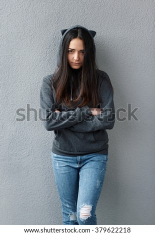 offended  black-haired girl in hoodie looking at camera. Wall background. - stock photo