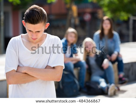 Offended boy teenager standing lonely while others talking outdoors