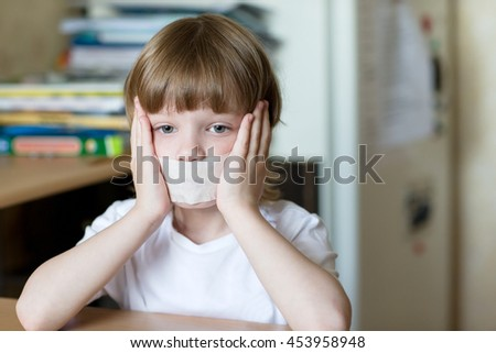Offended child sits at a table with his mouth sealed with tape. The concept of domestic violence and child protection. - stock photo