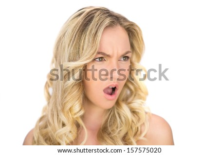 Offended curly haired blonde posing on white background