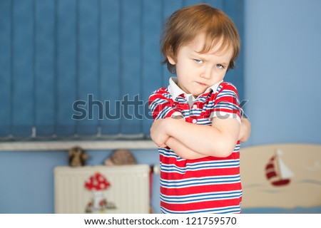 Offended little boy in his room - stock photo