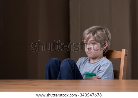 Offended little child sitting at the desk - stock photo