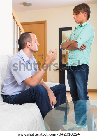 Offended man talking about problems  with teenager son - stock photo