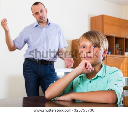 Offended teenager having conflict of arguing with father at home  - stock photo