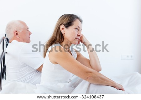offended woman sitting on   bed next to   frustrated man.