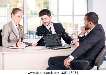 Office affairs. Three successful business people sitting in the office and do business while businessmen communicate with each other and work at a laptop - stock photo