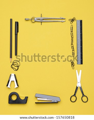 Office and back to school supplies on a yellow background. Looking down on the all black and chrome tools from an overhead angle. The items are arranged in a rectangle forming a frame.  - stock photo