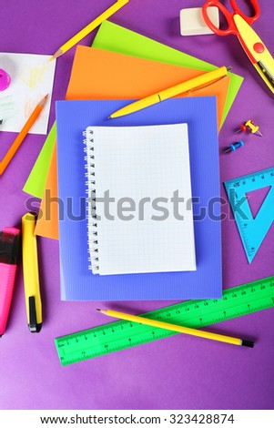 Office and student tools on purple background closeup - stock photo