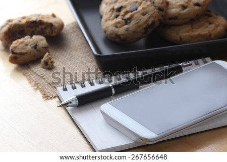 Office book with a pen and smartphone, cookie - stock photo