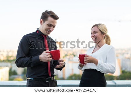 Office break man and woman talking and drinking from cups - stock photo