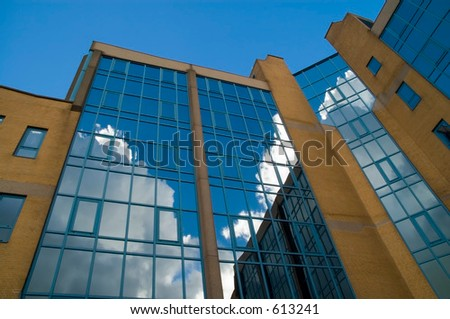 Office building at an angle with reflection of clouds (series 3) - stock photo