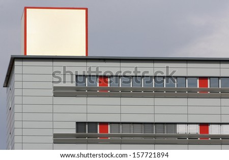 office building with grey walls and advertising cube on the roof - stock photo