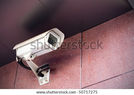 Office building with white security camera under a ceiling - stock photo