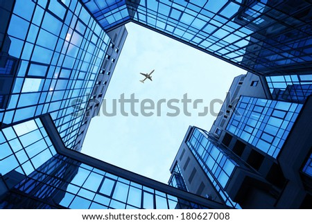 office buildings as a frame with blue sky and airplane - stock photo