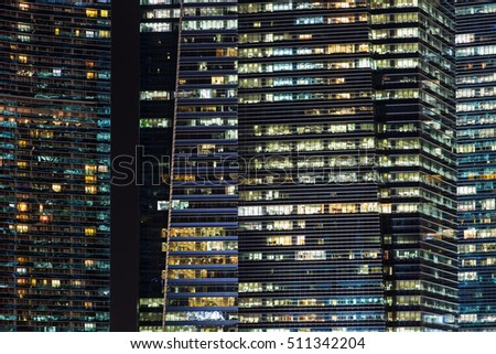 Office buildings at night in Singapore. Background with illuminated modern skyscrapers