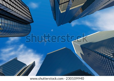 Office buildings with airplane on the blue sky - stock photo