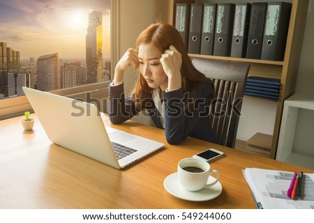 office, business, and finances concept, asian business woman feel exhausted about a crisis project with laptop computer and documents at office background