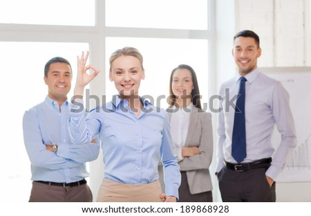office, business and teamwork concept - friendly young smiling businesswoman with team on back showing ok-sign - stock photo