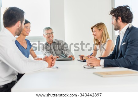 Office business meeting. The team is sitting at a table in a luminous white open space, brainstorming some new ideas. The men are wearing suits and shirts. They are laughing, smiling at each other