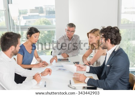 Office business meeting. The team is sitting at a table in a luminous white open space, brainstorming some new ideas. The men are wearing suits and shirts. The boss is exposing a new blueprint