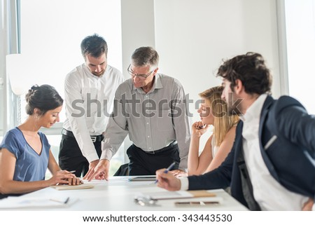 Office business meeting. The team is sitting at a table in a luminous white open space The men are wearing suits and shirts. The senior grey haired boss is up and showing a new design on his tablet