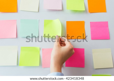 office, business, people and education concept - close up of hand with pen pointing to blank sticker on white board - stock photo