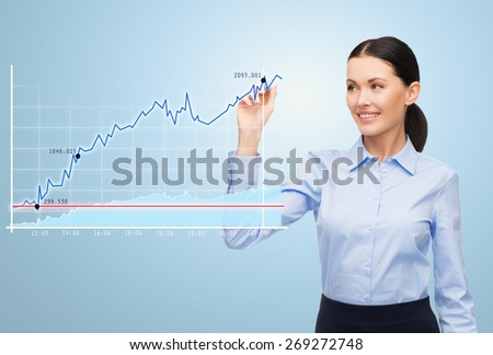 office, business, people and technology concept - businesswoman writing with marker and chart over blue background - stock photo