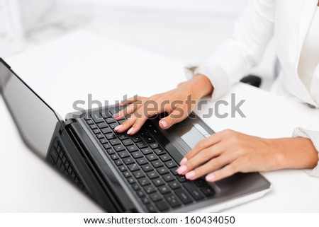 office, business, technology and internet concept - businesswoman using her laptop computer - stock photo