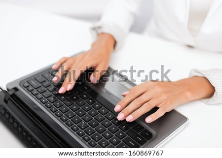 office, business, technology and internet concept - businesswoman using her laptop computer