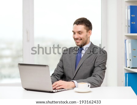 office, business, technology and internet concept - smiling businessman with laptop computer and coffee at office