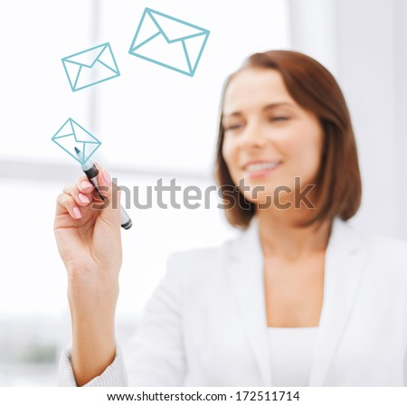 office, business, technology concept - businesswoman drawing envelopes in the air with marker - stock photo