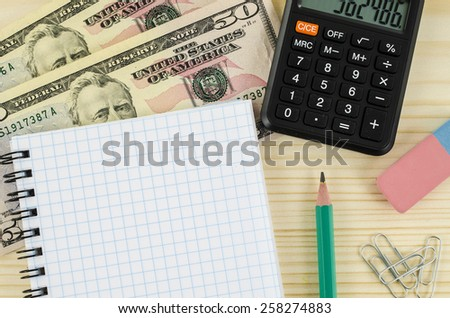 Office, business tools with dollars and calculator on wooden table