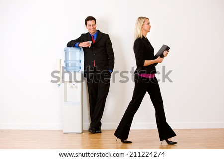 Office: Businessman Flirts With Coworker By Water Cooler - stock photo