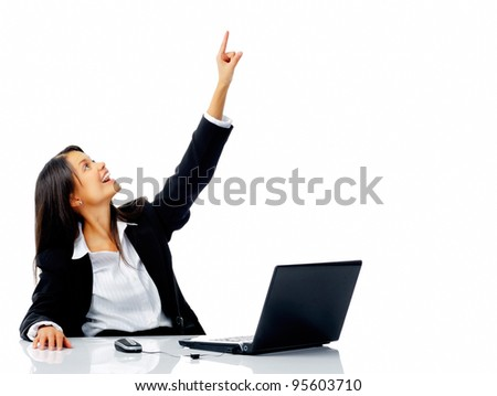 Office businesswoman pointing upward while sitting at her desk, isolated on white - stock photo