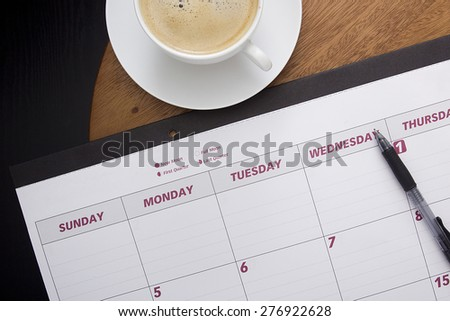 Office calendar planner on the coffee table with a cup of coffee. - stock photo