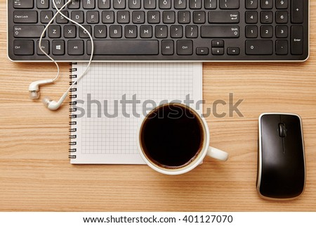 Office card. Keyboard, cup of coffee, headphones on a wooden background. Top view