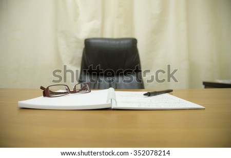 Office chair and desk of boss with notebook and pen and glasses create a comfortable workplace - stock photo