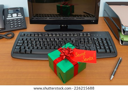 Office Christmas secret Santa gift wrapped present and tag on a desk - stock photo