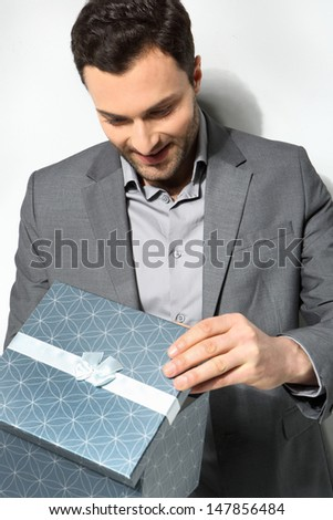 Office clerk with gift box on gray background
