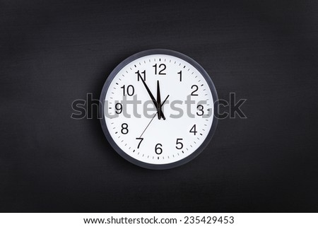 Office clock against chalkboard background