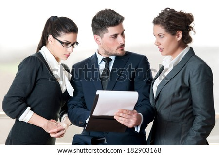 Office colleagues talking over clipboard - stock photo