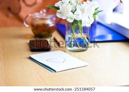 Office composition for St. Valentines Day: bouquet of white freesia flowers, smartphone, pen and notebook with painted heart. Selective focus on heart Blurred multicolored background. Horizontal image