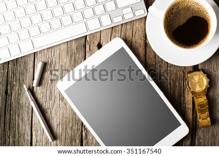 Office concept. Keyboard, tablet pc, and coffee on old wooden table - stock photo