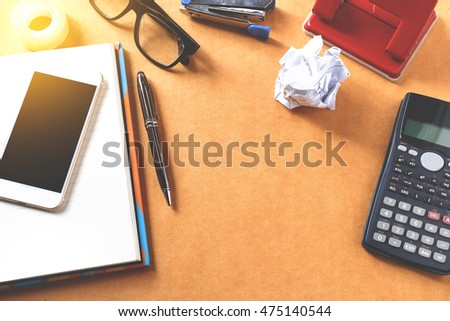 Office desk background with calculator, eye glasses on notepad and Office supplies, gadgets, View from above with copy space. soft focus.