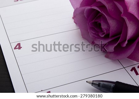Office desk calendar with a purple flower. - stock photo