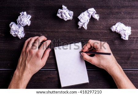Office desk, man writing note, studio shot, wooden background