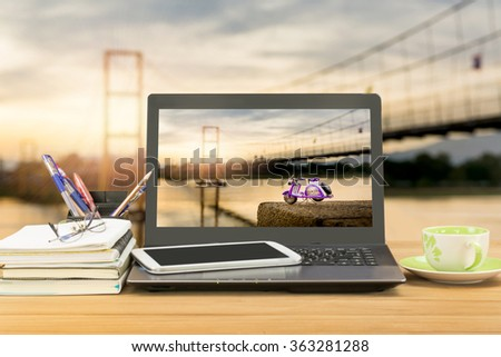 office desk,notebook computer,tablet,coffee cup,book,pen,pencil on wooden table over landscape of bamboo bridge with lighting of sunset background,selective focus at monitor - stock photo